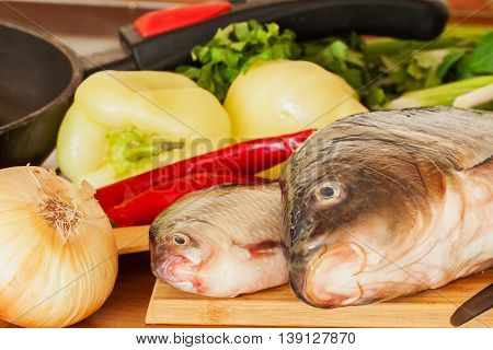 Two fresh raw river fishes, carp and crucian close up on a cutting board with onions, peppers, green herbs, red chili on table, next to frying pan, home cooking