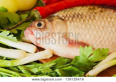 Crucian fish close up ready for cooking on the kitchen table with vegetables