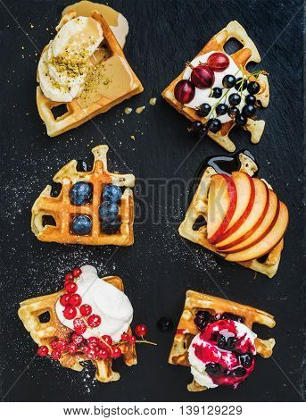 Warm belgian homemade waffles with fresh garden berries, fruit and ice cream on dark slate stone background, top view