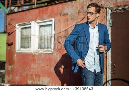 Stylish man in glasses stands outdoors on the decrepit building background. He wears blue jeans, a light shirt and a blue jacket. Guy looks to the right. Horizontal.