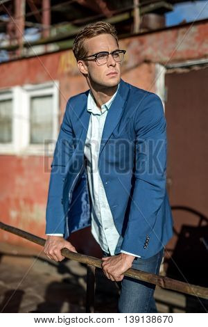 Trendy man in glasses stands outdoors on the decrepit building background. He wears blue jeans, a light shirt and a blue jacket. Guy looks to the left and holds his hands on the crossbar. Vertical.