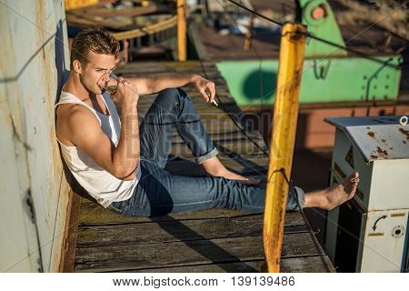 Trendy barefoot guy in a white singlet and blue jeans lies on the wooden surface in the industrial zone. He drinks from the glass in the right hand, left hand holds a cigarette. Outdoors. Horizontal.