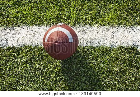 A leather college style football on a yard line viewed from above