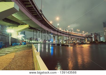 empty embankment with hanged highway structure by night at Sumida river in Tokyo Japan