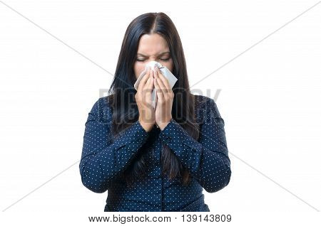 Young woman suffering from seasonal influenza or hay fever blowing her nose on a white tissue upper body in a stylish blue shirt isolated on white