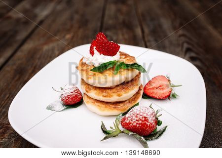 Pancakes pile with strawberry on wooden background. Rustic homemade dessert with flapjack and fresh berries