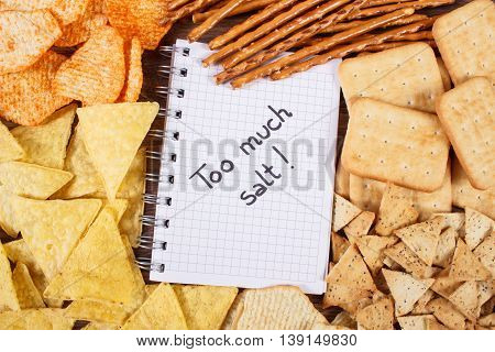Inscription Too Much Salt In Notebook And Heap Of Unhealthy Food