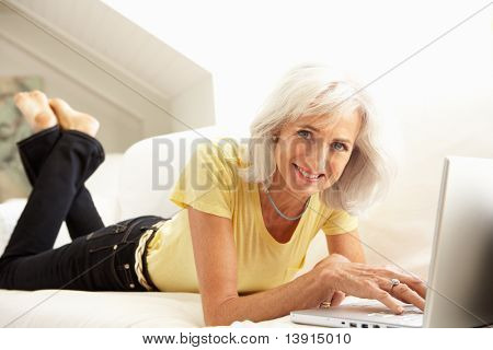 Senior Woman Using Laptop Relaxing Sitting On Sofa At Home