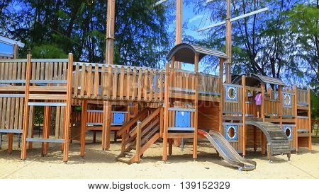 ship-shaped wooden jungle gym with slides, masts, wooden steps, tunnels, overhead walkway, under the pine trees on beach sand, Songkhla, Thailand