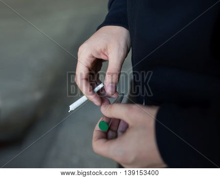 drug use, substance abuse, addiction, people and smoking concept - close up of addict hands with marijuana joint and blunt tube on street