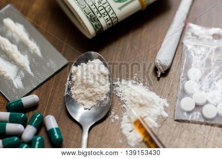 drug use, crime, addiction and substance abuse concept - close up of drugs with  money, spoon and syringe