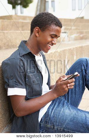 Étudiant adolescent assis extérieur sur marches de collège à l'aide de téléphone portable