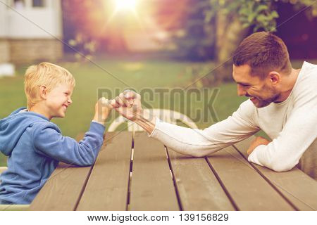 family, happiness, generation, home and people concept - happy father and son doing arm wrestling outdoors poster