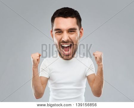 emotion, success, gesture and people concept - young man celebrating victory and screaming over gray background  (funny cartoon style character with big head)