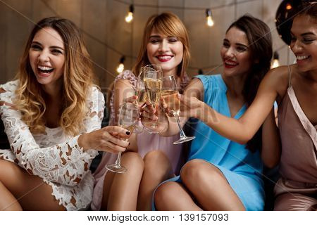 Four young beautiful girls in dresses smiling, laughing, clinking glasses with champagne at party.