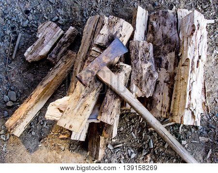 Cut logs firewood and old axe texture background