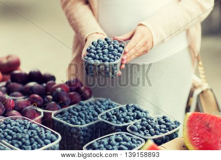 sale, shopping, pregnancy and people concept - close up of pregnant woman choosing blueberries at street food market