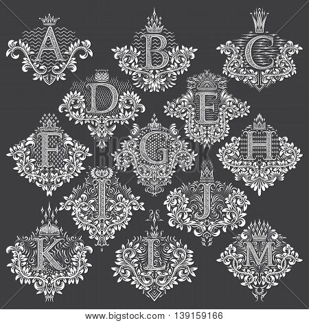 Set of heraldic monograms in coats of arms form. White floral decorative stamps of letters from A to M. Isolated tattoo labels in vintage baroque style.