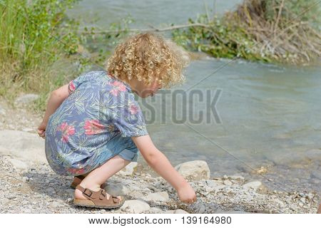 a little boy with blond hair plays the waterside