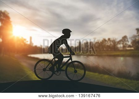 Silhouette Of A Man On Muontain Bike On Public Park At Sunset.
