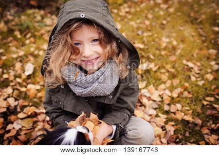 happy child playing with leaves in autumn. Seasonal outdoor activities with kids. Lifestyle capture on the walk.