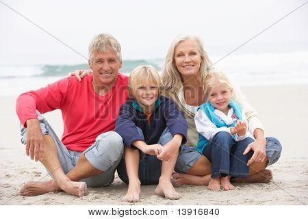 Grandparents And Grandchildren Sitting On Winter Beach Together
