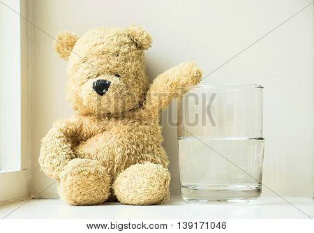 Bear is sitting down with a half glass of water