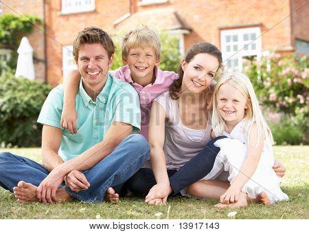 Rodzina siedzi w ogrodzie razem