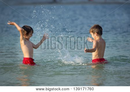 Two Sweet Children, Splashing Each Other With Water On The Beach