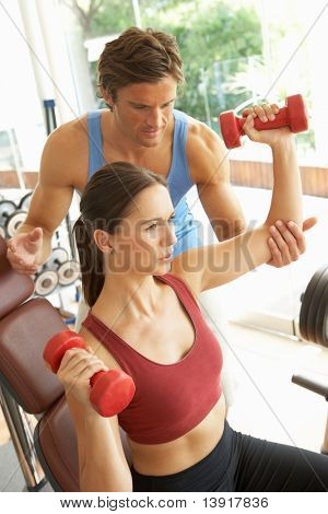 Young Woman Working With Weights In Gym With Personal Trainer