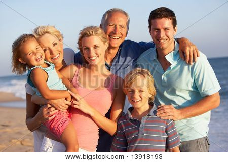 Retrato de familia de tres generaciones en vacaciones en la playa