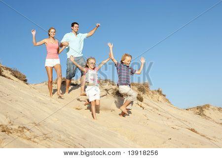 Familia disfrutando de vacaciones en la playa corriendo por Dune