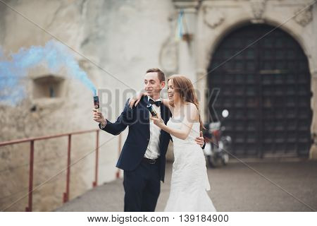 The bride and groom with smoke bombs on the background of castle.