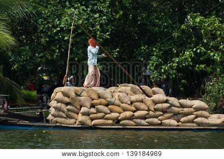 Allepey, Kerala, India March 31, 2015: Indian man transport dwell with rice for boats. backwaters canoe in state, . Cochin