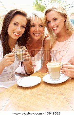Three Women Enjoying Cup Of Coffee In Cafe