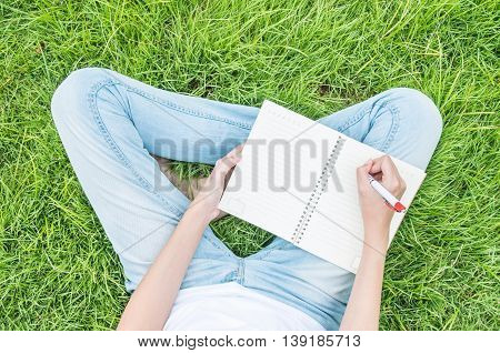Closeup asian woman sitting on grass field textured background for writing on note book under day light in the garden