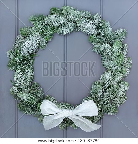 Snow covered christmas wreath of blue spruce fir with white bow on grey wood front door background.