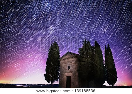Beautiful Tuscany night landscape with star trails on the sky, cypresses and a chapel. Natural outdoor amazing fantasy background.