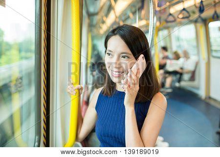 Woman talk to cellphone inside MTR in Hong Kong
