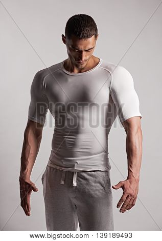 portrait of a gorgeous male model in tight clothes standing on grey background