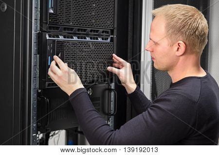 It engineer or technician work with servers in data rack. Shot in large datacenter.