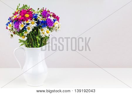 Wildflowers in white ceramic jug with copy space. Wild flower bouquet on white table. Bunch of wild herbs and flowers in a white jug. Wild flowers in a vase.