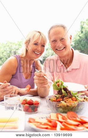Senior couple eating outdoors