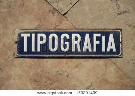 An old blue and white enamel tipografia sign on marble tiles. Tipografia means printer in Italian, Portuguese and Spanish.