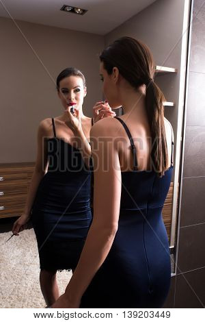 A young woman getting ready to go out, putting on lipstick in front of a mirror