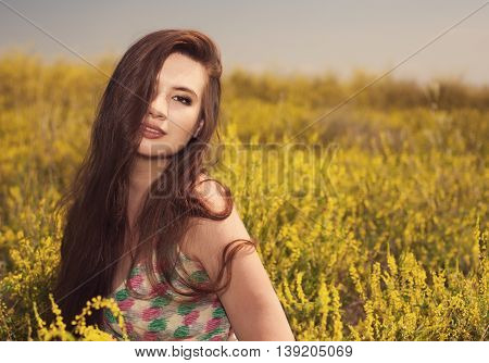 Young beauty woman in the park with yellow flowers photo