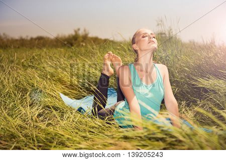 Young Blond Pretty Woman Doing Yoga Exercises On The Grass
