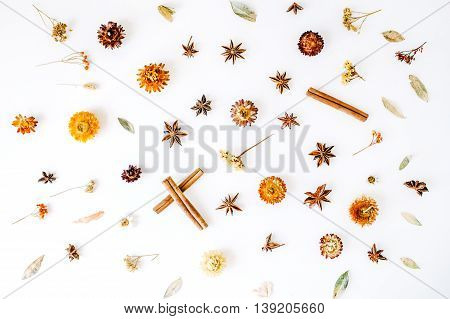 dry flowers cinnamon and cardamom pattern on white background. flat lay top view