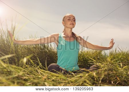 Blond Young Woman Meditating On The Nature With Eyes Closed