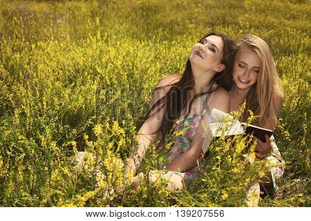 Two Beautiful Smiling Girls Reading Book Against Of Summer Park.